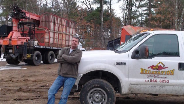 this is a photo of a man leaning on an excavation plus pickup truck at a job site, excavation plus, monson ma